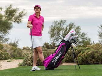 Lady Golfer next to Titleist Pink Out Golf Bag