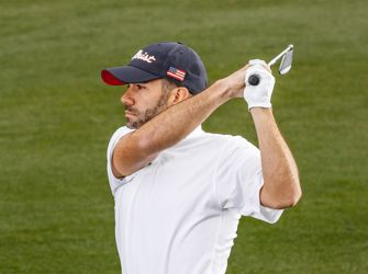 Golfer in Blue, White and Red Titleist Hat swinging a golf club