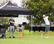 Golfer swinging club at fitting